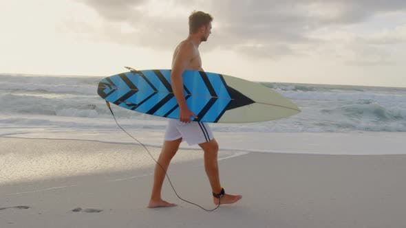 Man walking with surfboard at beach 4k