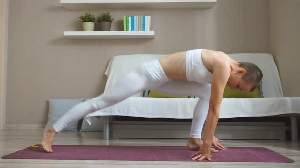 Young Healthy Caucasian Woman Practicing Yoga on the Mat in White Large Room.