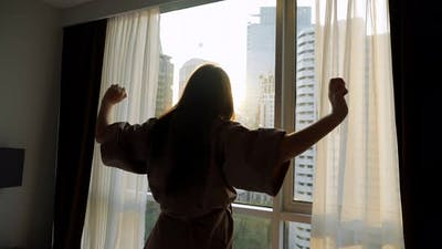 Silhouette of Woman Looking at Skyscrapers Outside Window