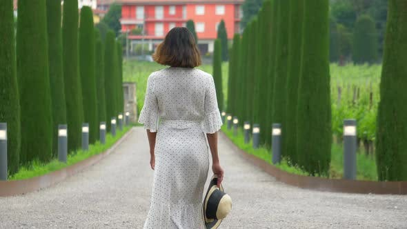 A woman walking on a path with cypress trees while traveling at a luxury resort in Italy, Europe