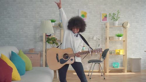 African American Woman with an Afro Hairstyle Expressive Playing on the Guitar