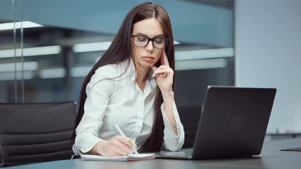Businesswoman in Eyeglasses Working on Laptop and Writing in Journal