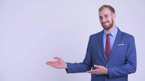 Happy Bearded Businessman Showing Something