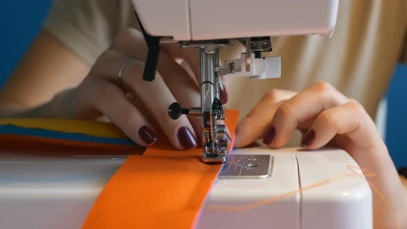 Thumbnail for the Dressmaker Girl Is Intently Stitching the Details of a Waist Bag on a Sewing Machine