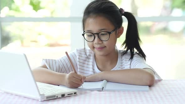 Beautiful Asian Girl Wear Glasses Writing To Notebook On The Table