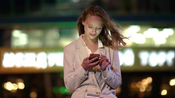 Thumbnail for Young Woman Charging Mobile Phone While Using It.
