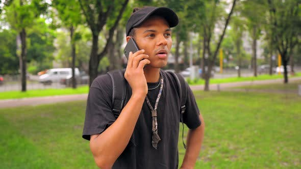 Thumbnail for Student with Backpack Has Phone Conversation Outdoors