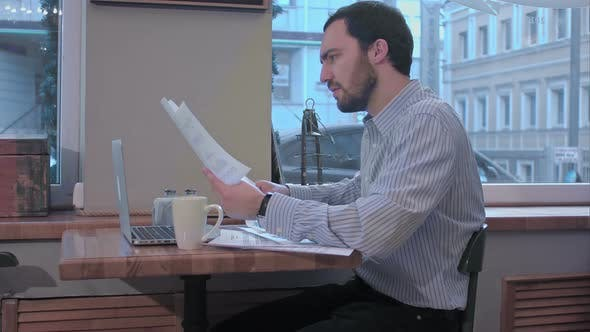 Thumbnail for Businessman in a Cafe Reading with Interest a Contract Document