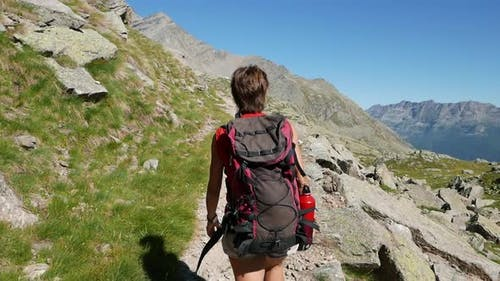 One person hiking on mountain top, Summer adventures on the Alps