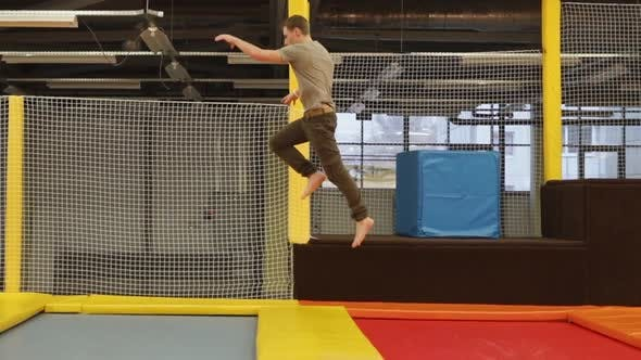 Male Acrobat Is Bouncing Through Few of Trampolines in a Gym