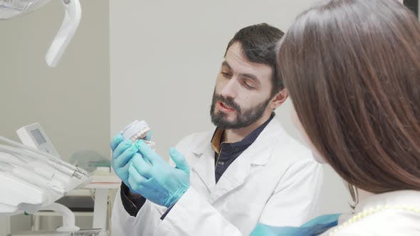 Professional Dentist Educating His Female Patient During Medical Appointment