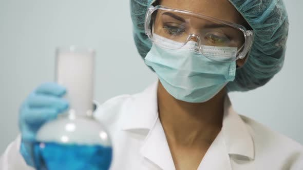 Cover Image for Female Chemist Holding Flask With Blue Evaporating Liquid in Hand, Experiment