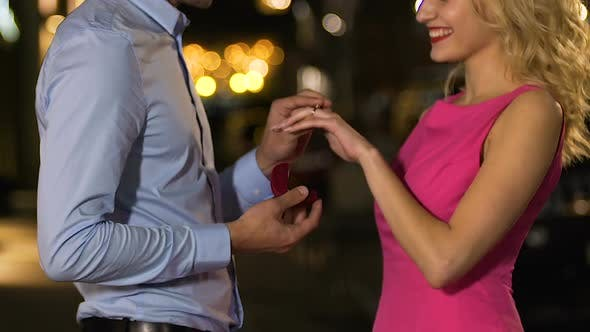Cover Image for Man Making Proposal with Engagement Ring, Putting on Girl Finger, Couple Hugging