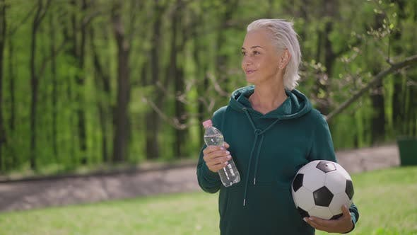 Live Camera Zoom in to Smiling Satisfied Senior Caucasian Sportswoman Standing with Soccer Ball and