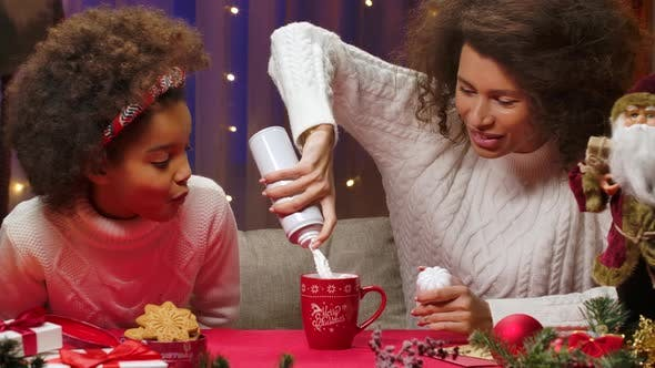 Thumbnail for African American Mom and Little Daughter in White Sweaters Have Fun and Taste Whipped Cream with