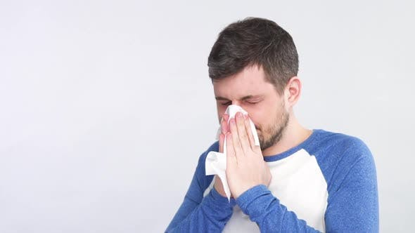 Thumbnail for Sick Man with Symptoms of Flu Sneezing Nose in White Tissue Isolated on Grey Background