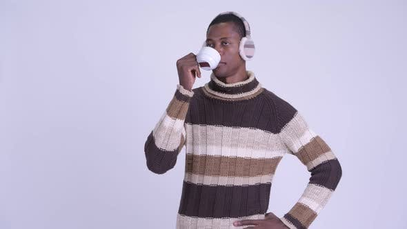 Thumbnail for Young Happy African Man Thinking While Drinking Coffee Ready for Winter
