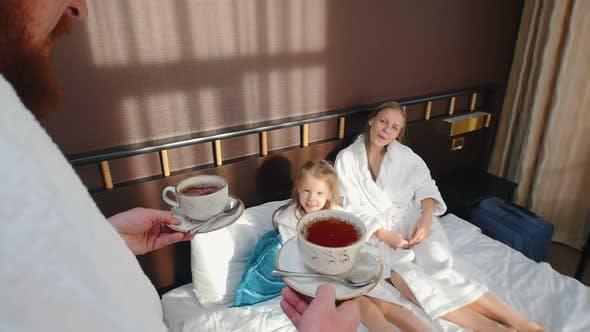 L' homme apporte les tasses à thé au lit
