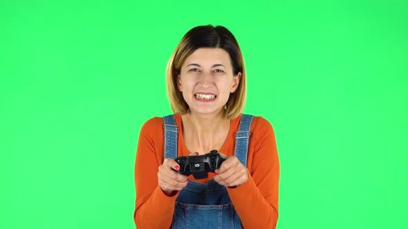 Cover Image for Girl Playing a Video Game Using a Wireless Controller with Joy and Rejoicing in Victory. Green