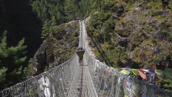 Thumbnail for Porter Is Walking on Suspension Bridge in Khumbu. Himalaya, Nepal