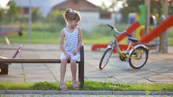 Cute little girl sitting on a bench and riding a bicycle on a school yard in summer.