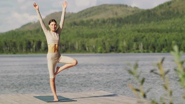 Beautiful Yogini Practicing Tree Pose in Nature