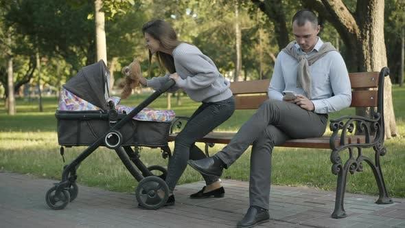 Thumbnail for Weite Aufnahme der fröhlichen kaukasischen Mutter, die Teddybären mit dem Kleinkind im Kinderwagen spielt, wie konzentriert