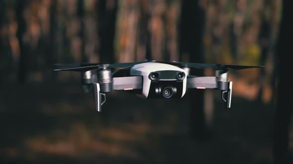 Thumbnail for Drohne mit einer Kamera schwebt in der Luft. Fliegen über dem Boden im Wald. Zeitlupe