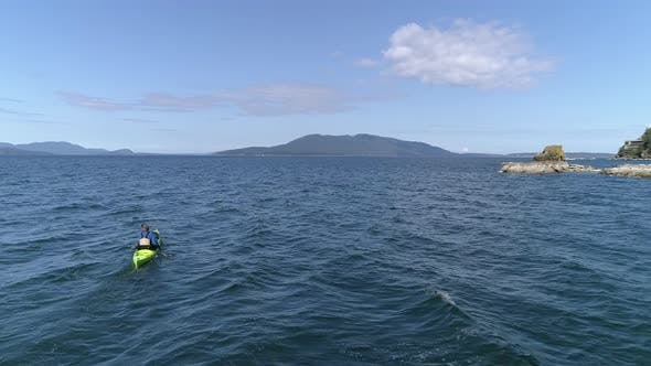Thumbnail for Ocean Kayak Aerial Flying High To Low On Man Paddling Blue Coastal Waters