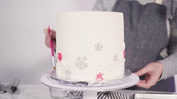 Thumbnail for Step by step. Decorating round funfetti cake with pink and white fondant snowflakes.