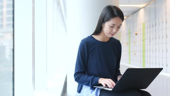 Thumbnail for Woman doing homework on laptop computer inside university campus