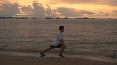 A handsome Asian sportsman stretching exercises before running exercise outside on the beach.
