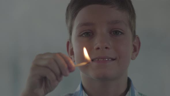 Thumbnail for Close-up Face of Little Boy Playing with the Matches in the Dark Smoky Room. The Child Lit the Match