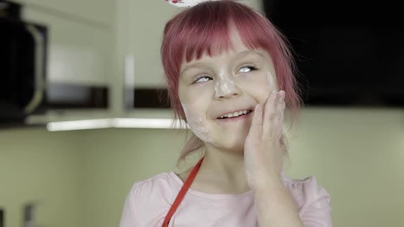 Thumbnail for Little Child Girl in the Kitchen Dressed in Apron and Scarf. Face in Flour