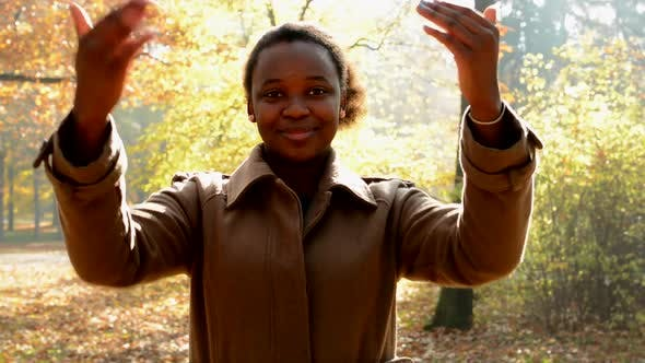Thumbnail for A Young African Girl Stands in the Woods, Stare To Camera and with Her Hands Shows To Oneself
