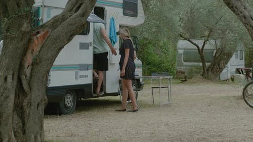 Traveler couple go to motor home RV campervan. Traveling in recreational vehicle