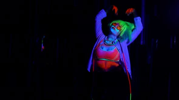 Gogo Dancer Woman is Moving in Nightclub Fluorescent Makeup and Wig in UV Lights on Dance Floor