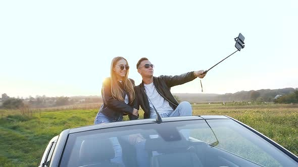 Thumbnail for Attractive Man and Woman Taking Selfie While Sitting in the Cabriolet