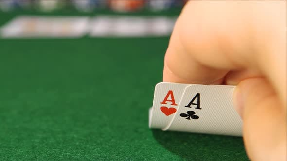 Thumbnail for POKER: The player's hand opens and looks his cards on a table