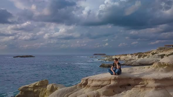 Thumbnail for A Girl Sits on a Rock on the Sea Coast