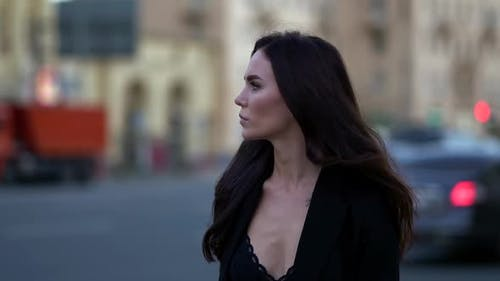 Fashion Model Woman Is Walking in Twilight on City Street, Medium Portrait