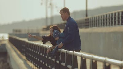Husband and Wife Stand at the Parapet and Hold Their Little Son