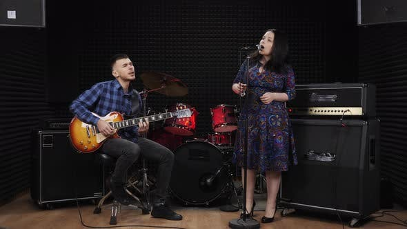 Woman and man are emotionally singing lyric songs on stage at recording vocal studio