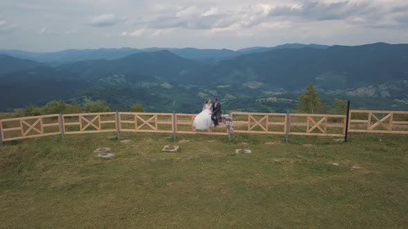 Thumbnail for Groom with Bride Sit on the Fence Near Mountain Hills. Aerial Drone Shot