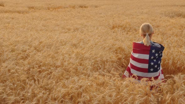 Thumbnail for Woman with USA Flag on Her Shoulders Stands in a Wheat Field