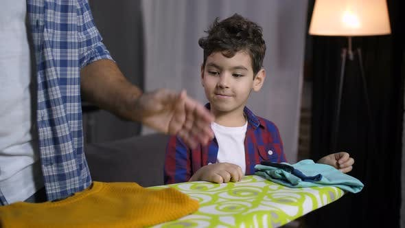 Thumbnail for Son Helping Dad To Fold Ironed Clothes at Home