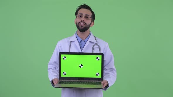 Cover Image for Happy Young Bearded Persian Man Doctor Talking While Showing Laptop