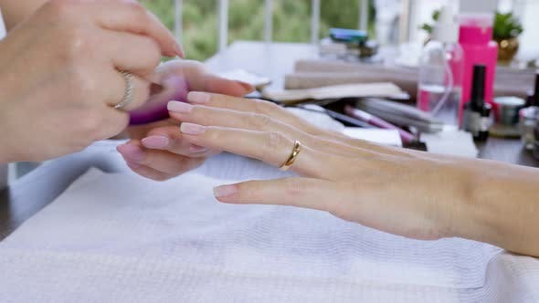 Manicurist cleaning clients hand with brush.