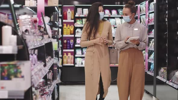 Beauty Advisor And Female Customer In Masks in Make-Up Shop