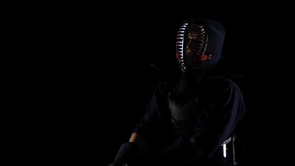 Cover Image for Masculine Kendo Warrior Practicing Martial Art with the Bamboo Bokken on Black Background. Slow